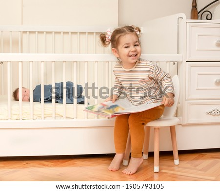 Cute portrait of toddler sister with  baby brother. Little girl playing with her newborn brother. Big sister meet her infant brother first time after his born. Family with 2 children. Real people. Foto stock ©