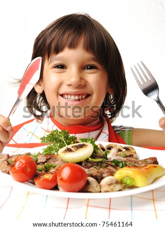 Cute positive boy with fork and knife eating on lunch table