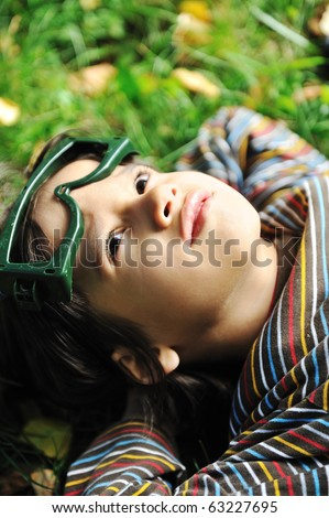 Cute positive boy with glasses  laying on green grass ground and looking up - stock photo