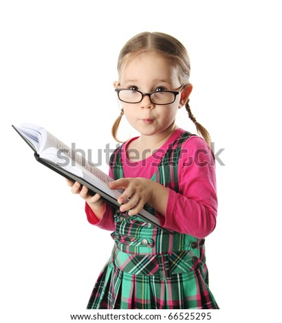 Cute preschool age girl wearing eyeglasses looking at a book