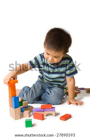 Cute preschool boy concentrating, playing with wooden blocks. Isolated studio shot on white. - stock photo