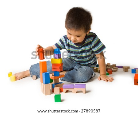 Cute preschool boy playing with wooden blocks. Isolated studio shot on white.