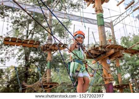 Cute preschool girl and boy having fun and enjoying their time in a rope playground structure at adventure park, outdoor family weekend activities, happy summertime, sport and active lifestyle