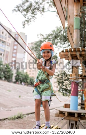 Cute preschool girl having fun and enjoying her time in a rope playground structure at adventure park, outdoor family weekend activities, happy summertime, sport and active lifestyle