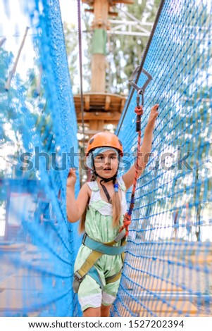 Cute preschool girl having fun and enjoying their time in a rope playground structure at adventure park, outdoor family weekend activities, happy summertime, sport and active lifestyle
