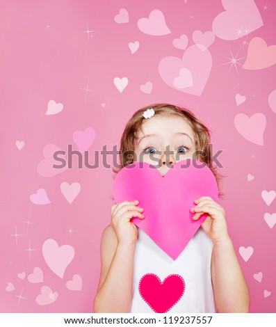 Cute preschool girl holding pink paper heart in hands