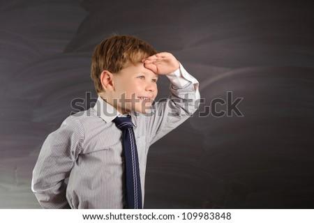 Cute preschooler against dark blackboard in classroom