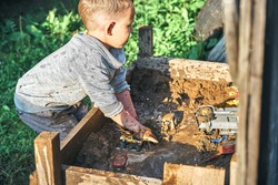 Cute preschooler boy with dirty face and clothes playing with toy cars in the sandbox near wooden rural house in summer day in countryside
