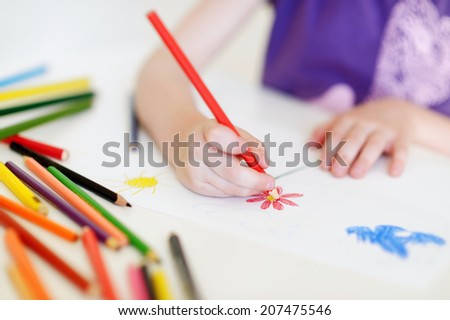 Cute preschooler girl drawing a picture with colorful pencils