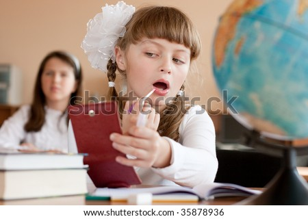 stock photo : Cute preteen schoolgirl is making make-up during lesson at