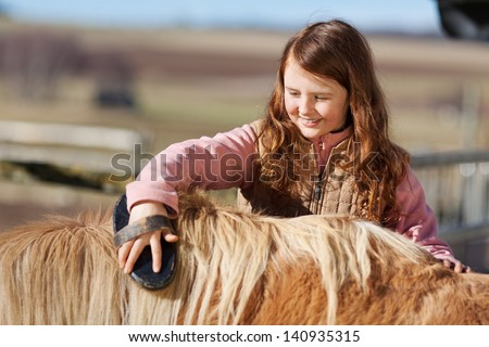 Cute pretty little teenage girl reaching over and brushing the mane of her pet pony