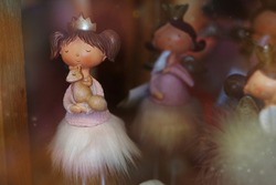 Cute princess toy in a delicate dress. Ceramic doll. Blurred background