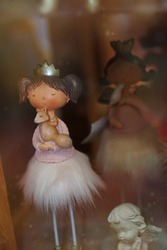 Cute princess toy in a delicate dress. Ceramic doll with a squirrel in hands. Magical girl in pink fluffy skirt and gold crown. Toy shop. Store of interesting toys. A wonderful gift for a little girl
