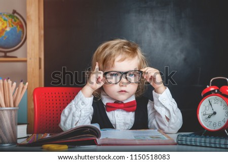 Cute pupil from primary school is sitting at desk in a glasses with raising hand. Child is ready to answer with a blackboard on a background. Back to school. Pencils, alarm clock, globe and books #1150518083