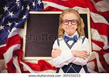 Cute pupil with arms crossed against american flag on chalkboard