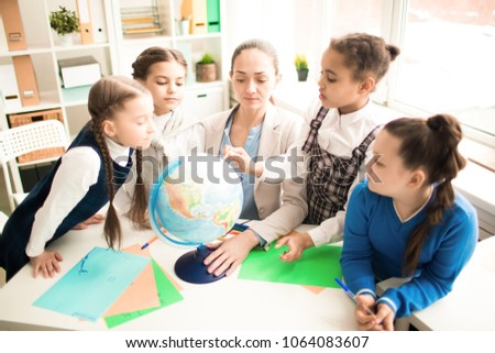 Cute pupils and teacher in classroom with globe at the primary school #1064083607
