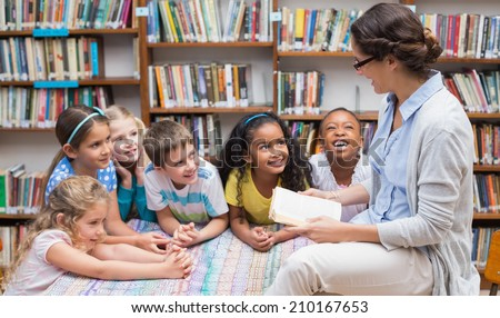 Cute pupils and teacher reading in library at the elementary school #210167653