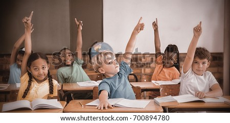 Cute pupils raising their hands at elementary school #700894780