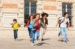 Cute pupils running  from school building