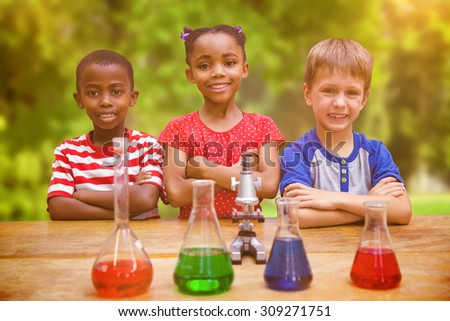 Cute pupils standing with arms crossed behind beaker against trees and meadow