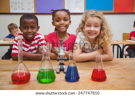 Cute pupils standing with arms crossed behind beaker at the elementary school
