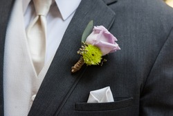 Cute purple boutonniere and a white hanker-chief in pocket.