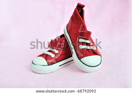 cute red baby shoes in soft selective focus - stock photo