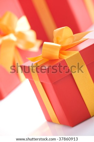 Cute red gift boxes with gold ribbon on white background. Photo taken at an angle