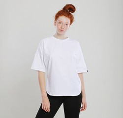 Cute red-haired girl posing in a  oversize shirt against the gray background