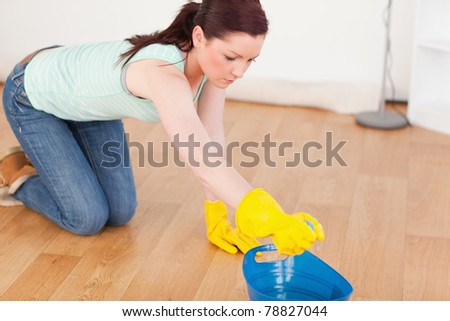 Cute red-haired woman cleaning the floor while kneeling at home