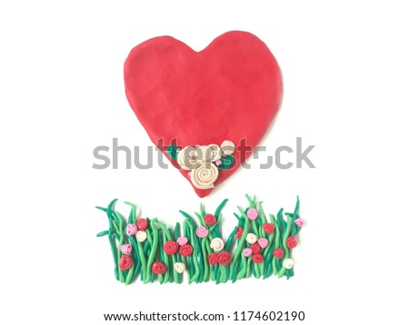 Cute red heart beautiful decoration over on grasses made from plasticine clay dough placed on white background, Love and care for nature #1174602190