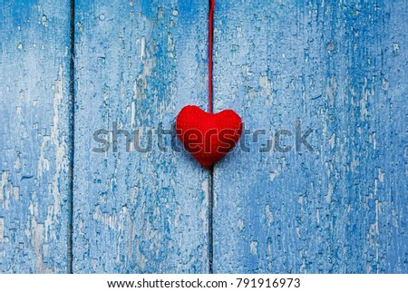 cute red heart knitted of yarn hanging on the wall with old peeling blue paint #791916973