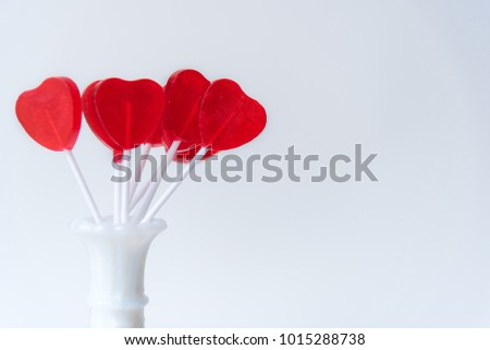Cute red heart-shaped lollipops displayed in white vase against white background #1015288738