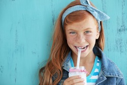 Cute redheaded child drinking milk on vintage blue background