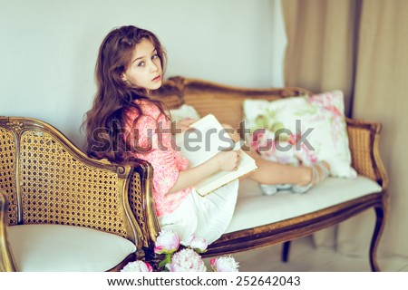 Cute sad girl baby with gorgeous hair in the skirt and the sweater is reading a book, sitting on the sofa ,in the interior
