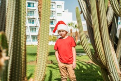 Cute sad little boy in red santa hat playing on tropical beach.flight cancellation, sad, poor rest. Not a dream come true, lack of gifts, a holiday broke.Turkish or Egyptian hotel, cacti palm trees.