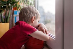 Cute sad little kid with football ball sitting on the window sill and looking on the street, dream about outdoor activity during quarantine lockdown, indoor lifestyle, concept of sorrow
