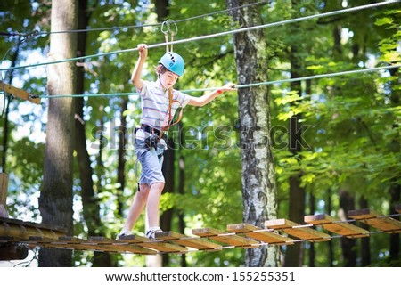 Cute school boy enjoying a sunny day in a climbing adventure activity park