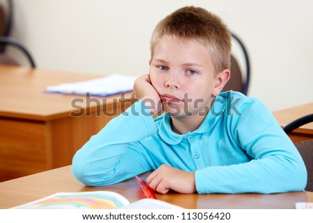 Cute schoolboy at workplace looking at camera in classroom