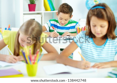 Cute schoolboy drawing at workplace with schoolmates on foreground