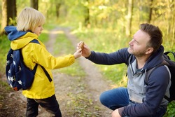 Cute schoolchild and his mature father hiking together and exploring nature. Little boy with his dad spend quality family time together in the sunny summer forest. Daddy and his little son
