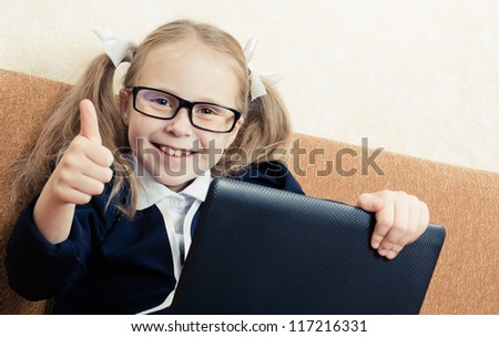 Cute schoolgirl in glasses with a laptop shows gesture okay.