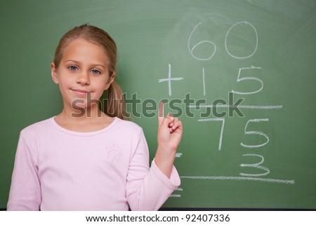 Cute schoolgirl raising her hand in front of a blackboard - stock photo