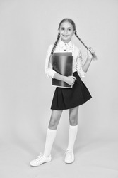 Cute schoolgirl. School education. Courses for gifted children. Basic level. Happy schoolgirl hold textbooks yellow background. Little schoolgirl back to school. Small schoolgirl wear uniform.