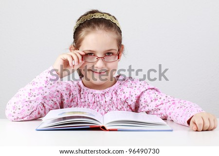 Cute schoolgirl with glasses reading book
