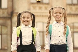 Cute schoolgirls with long ponytails looking charming. Ending of school year. Lucky to meet each other. Cheerful smart schoolgirls. Happy schoolgirls outdoors. Small schoolgirls wear school uniform