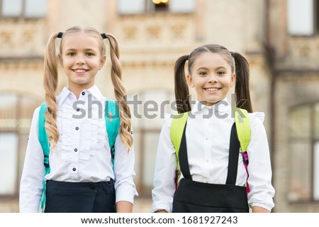 Cute schoolgirls with long ponytails looking charming. Ending of school year. Lucky to meet each other. Cheerful smart schoolgirls. Happy schoolgirls outdoors. Small schoolgirls wear school uniform.