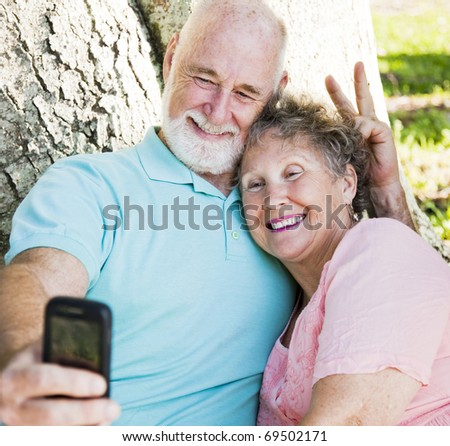 Cute senior couple taking their self portrait with their cellphone.  He's giving her rabbit ears.