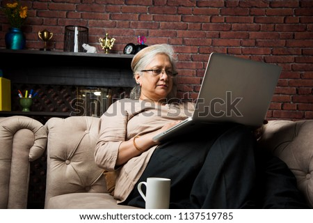 cute Senior indian/asian lady sitting on recliners chair or sofa reading book or using tab or laptop computer Stock foto ©