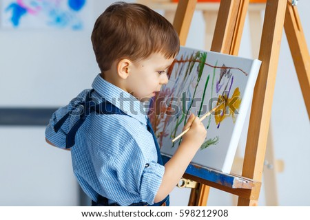 Cute, serious and focused, three years old boy in blue shirt and jeans apron drawing on canvas standing on the easel. Concept of early childhood education, painting, talent, happy family or parenting #598212908